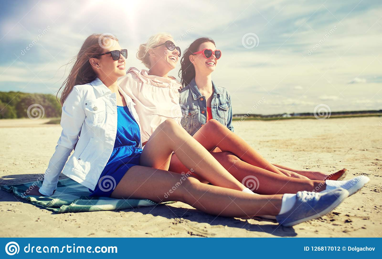 Grupp av att le kvinnor i solglasögon på stranden