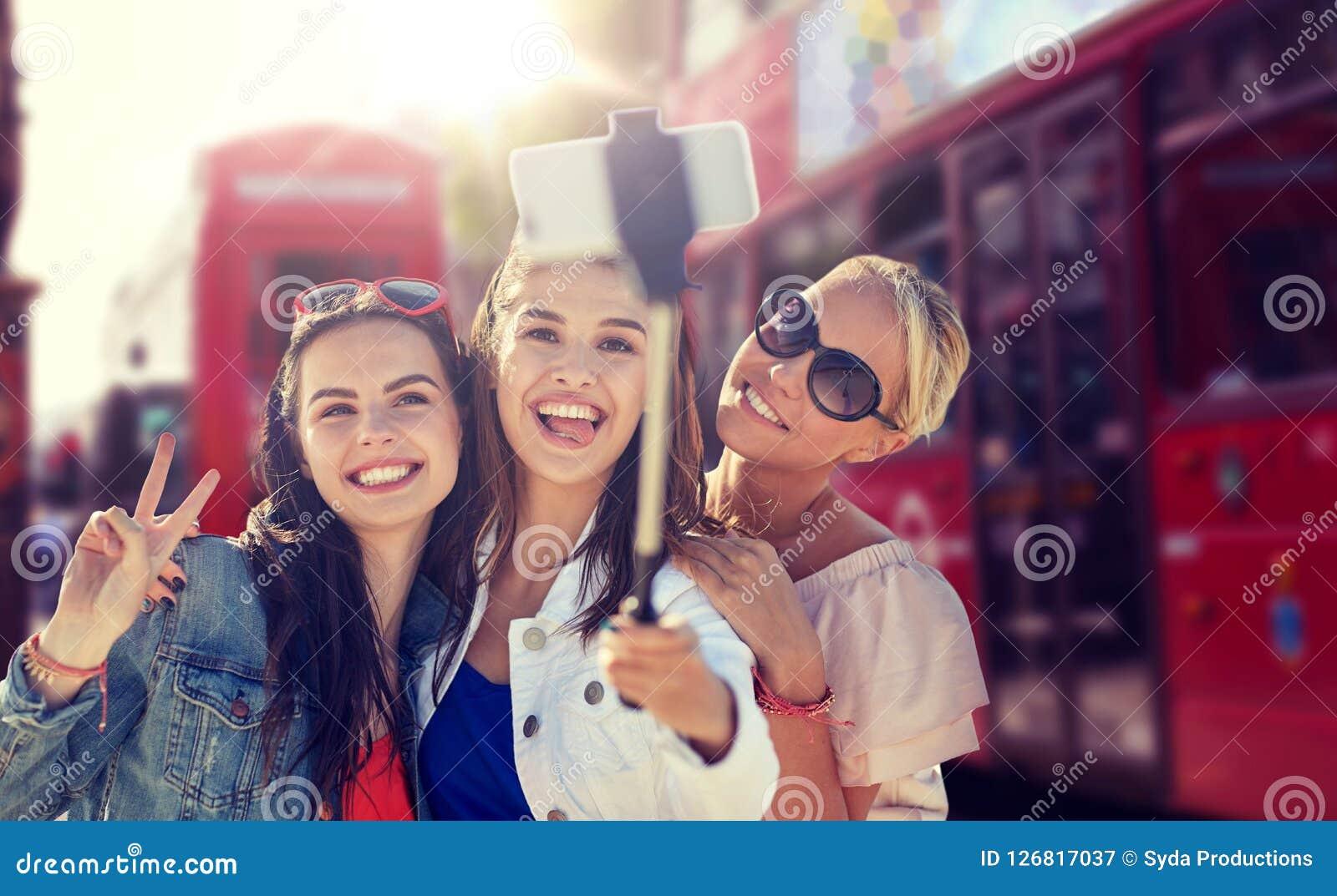 Grupp av att le kvinnor som tar selfie i london