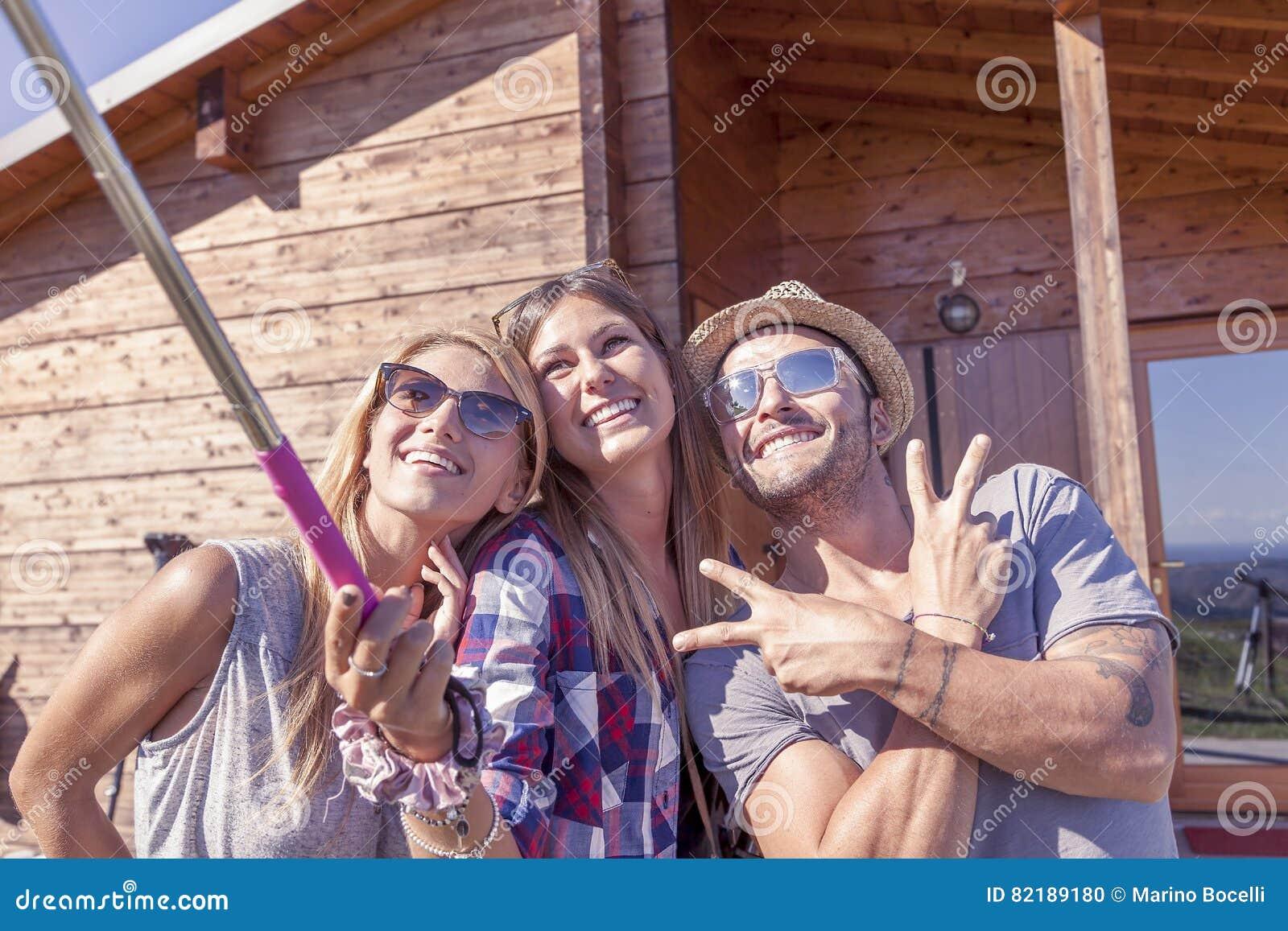 Grupp av att le vänner som tar rolig selfie med den smarta telefonen