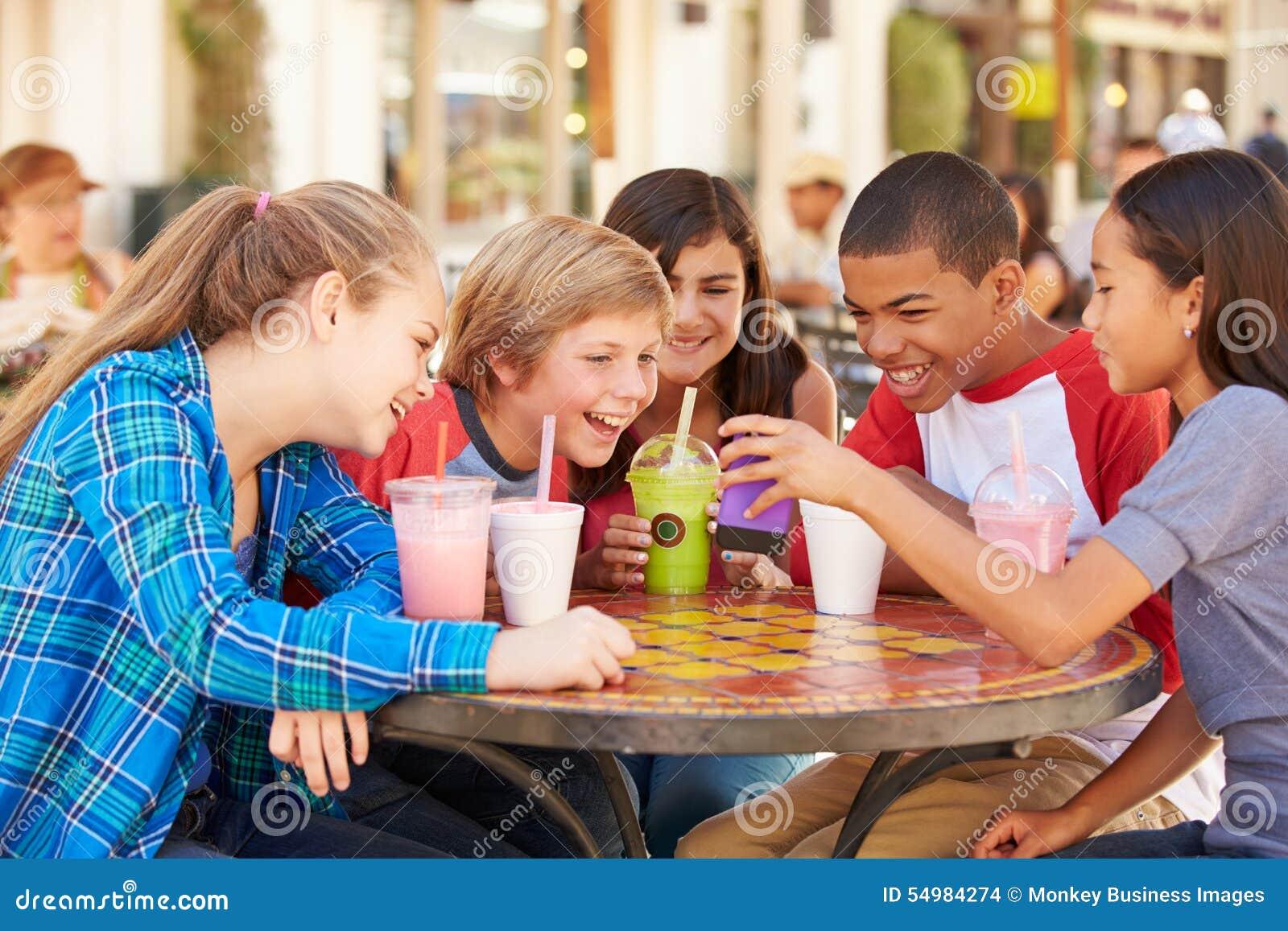 Grupp av barn i CafÅ ½ som ser text på mobiltelefonen
