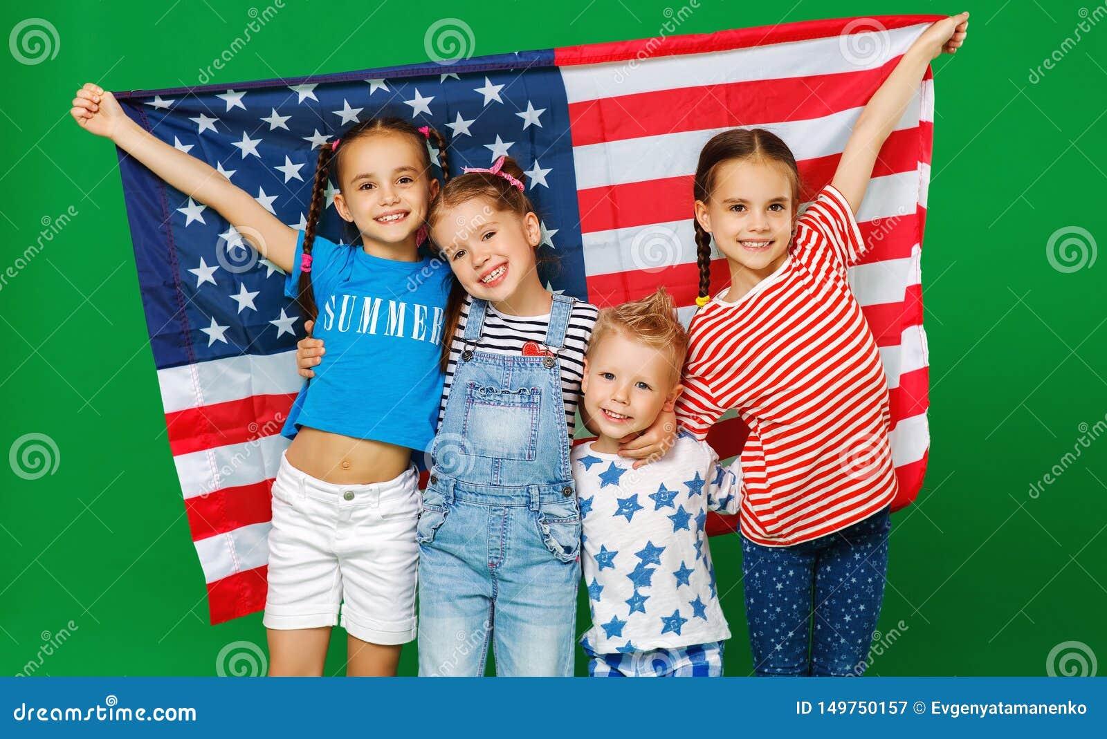 Grupp av barn med flaggan av Amerikas f?renta stater USA p? gr?n bakgrund
