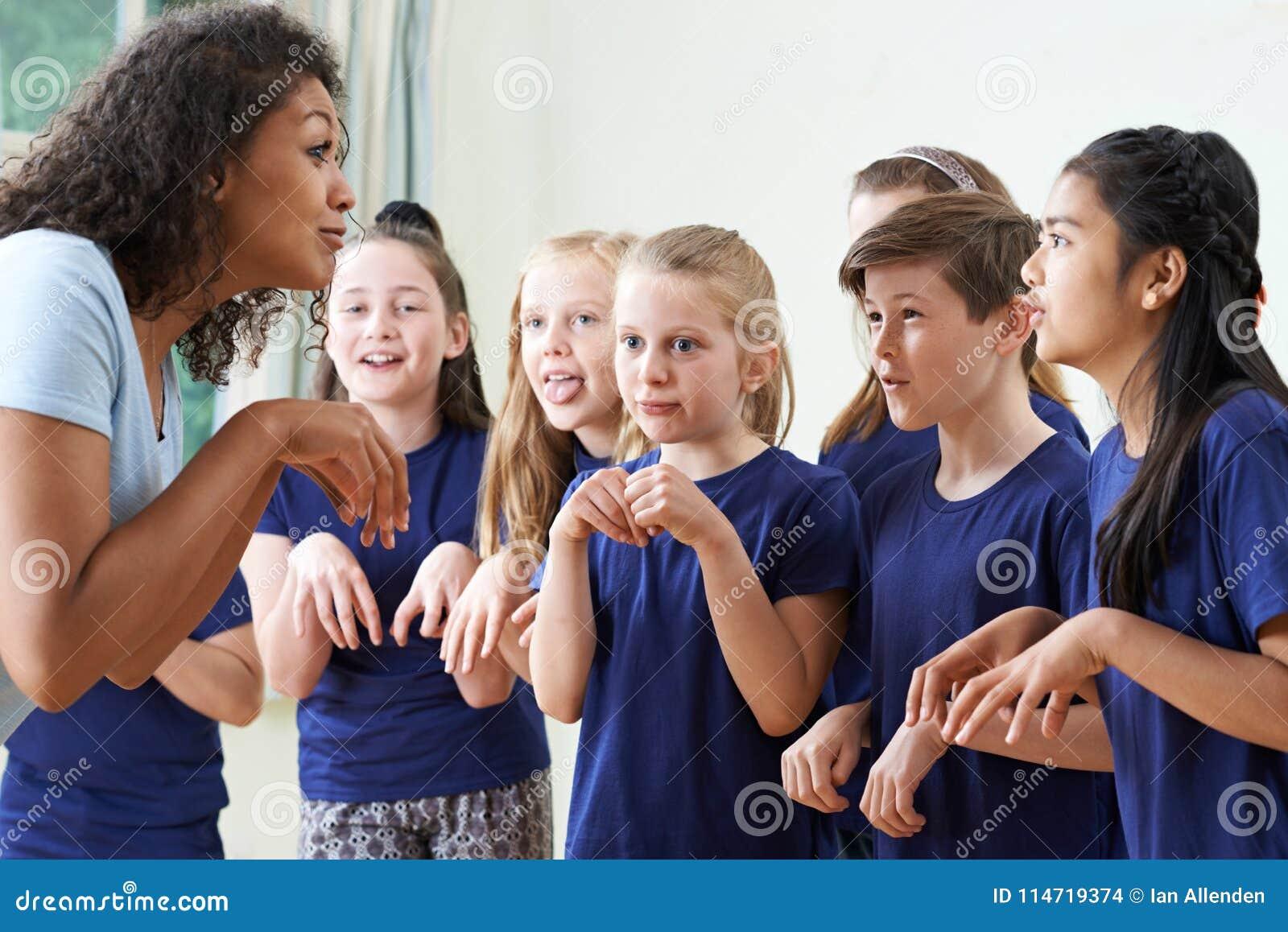 Grupp av barn med läraren Enjoying Drama Class tillsammans