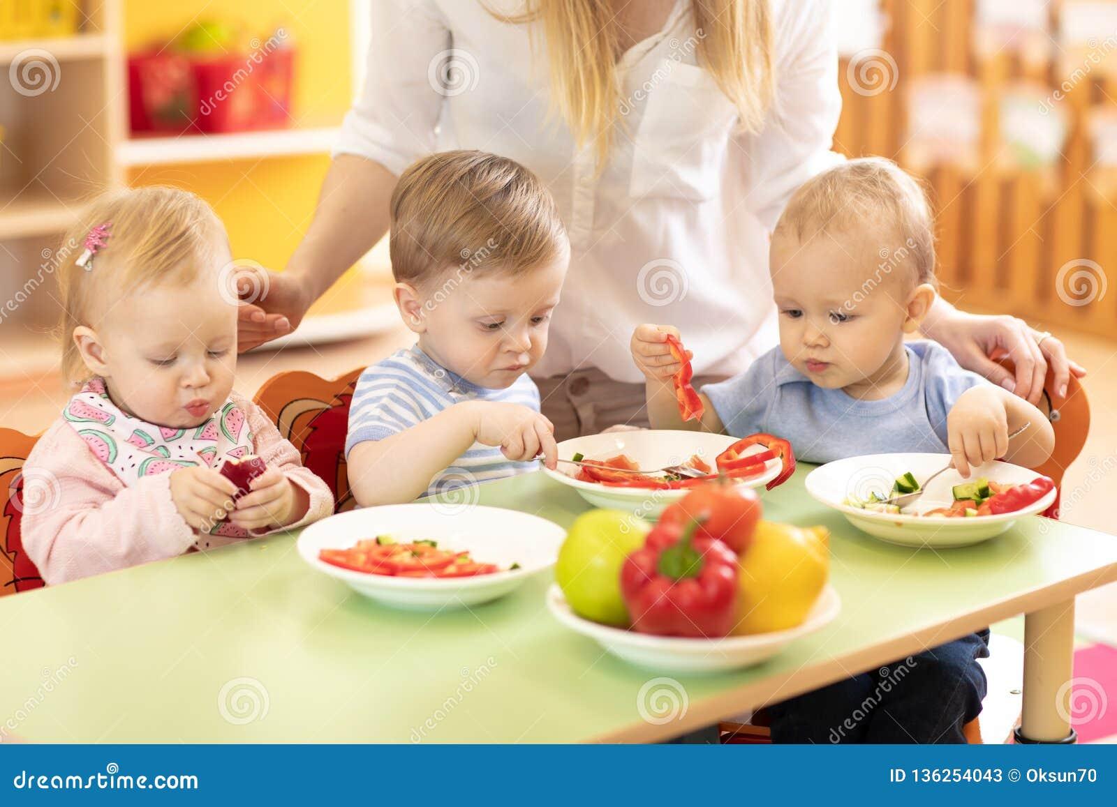 Grupp av barn som äter från plattor i daghem