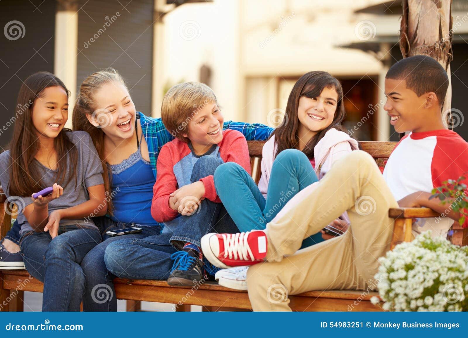 Grupp av barn som sitter på bänk i galleria