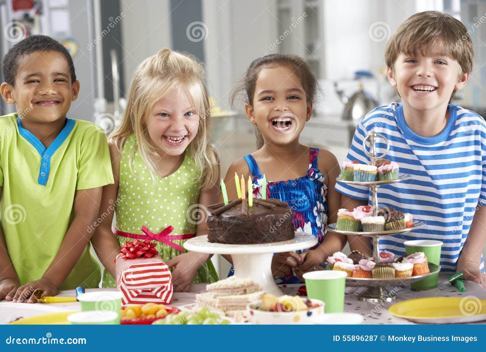 Grupp av barn som står vid tabellen som läggas med mat för födelsedagparti