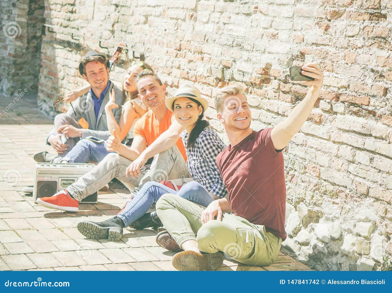 Grupp av blandras- vänner som tar en selfie med en mobil smartphonekamera - självstående av lyckliga personer