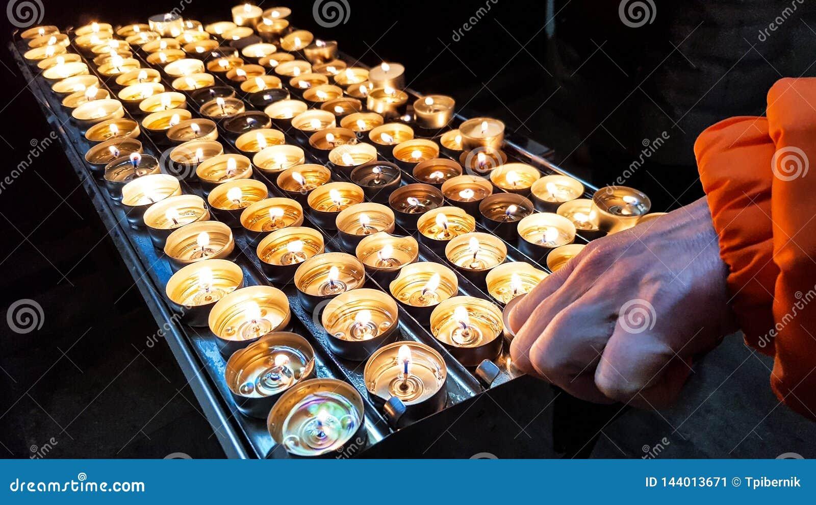Grupp av brännande stearinljus för skinande brand på en metallhållare