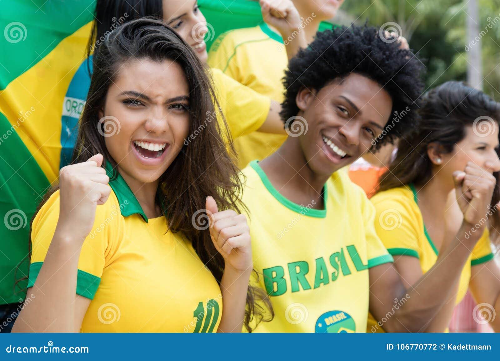 Grupp av brasilianska fotbollfans för bifall med flaggan av Brasilien
