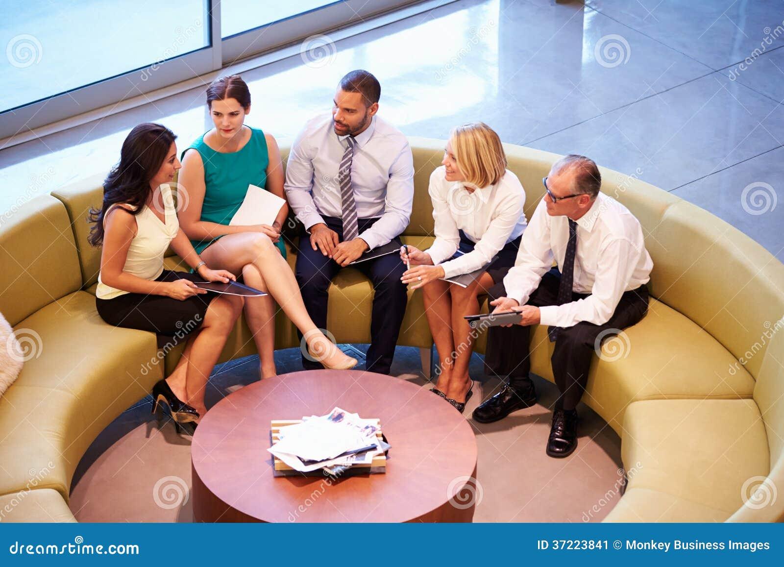 Grupp av Businesspeople som har möte i regeringsställning av lobbyen