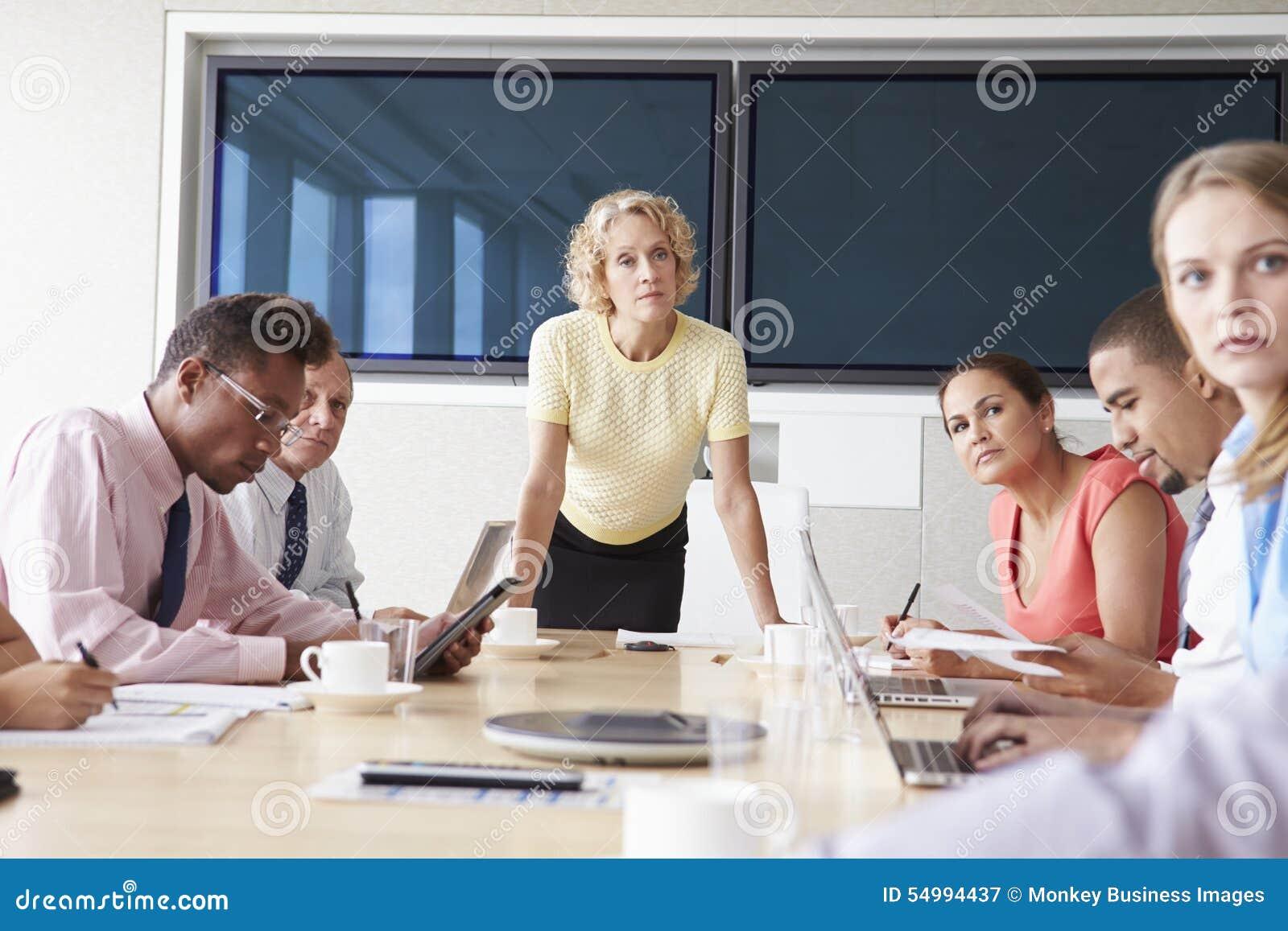 Grupp av Businesspeople som möter runt om styrelsetabellen