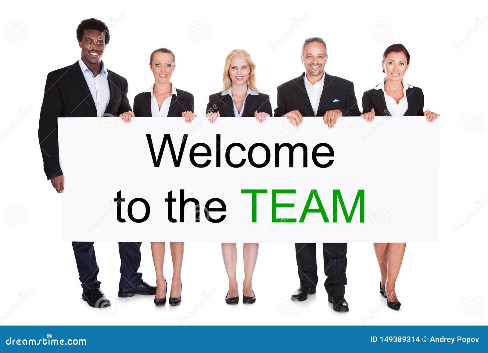 Grupp av Businesspeople som rymmer v?lkomnande till Team Placard