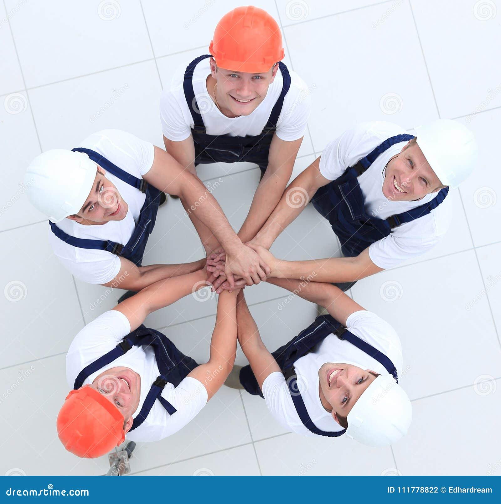 Grupp av byggnadsarbetare med händer som tillsammans knäppas fast