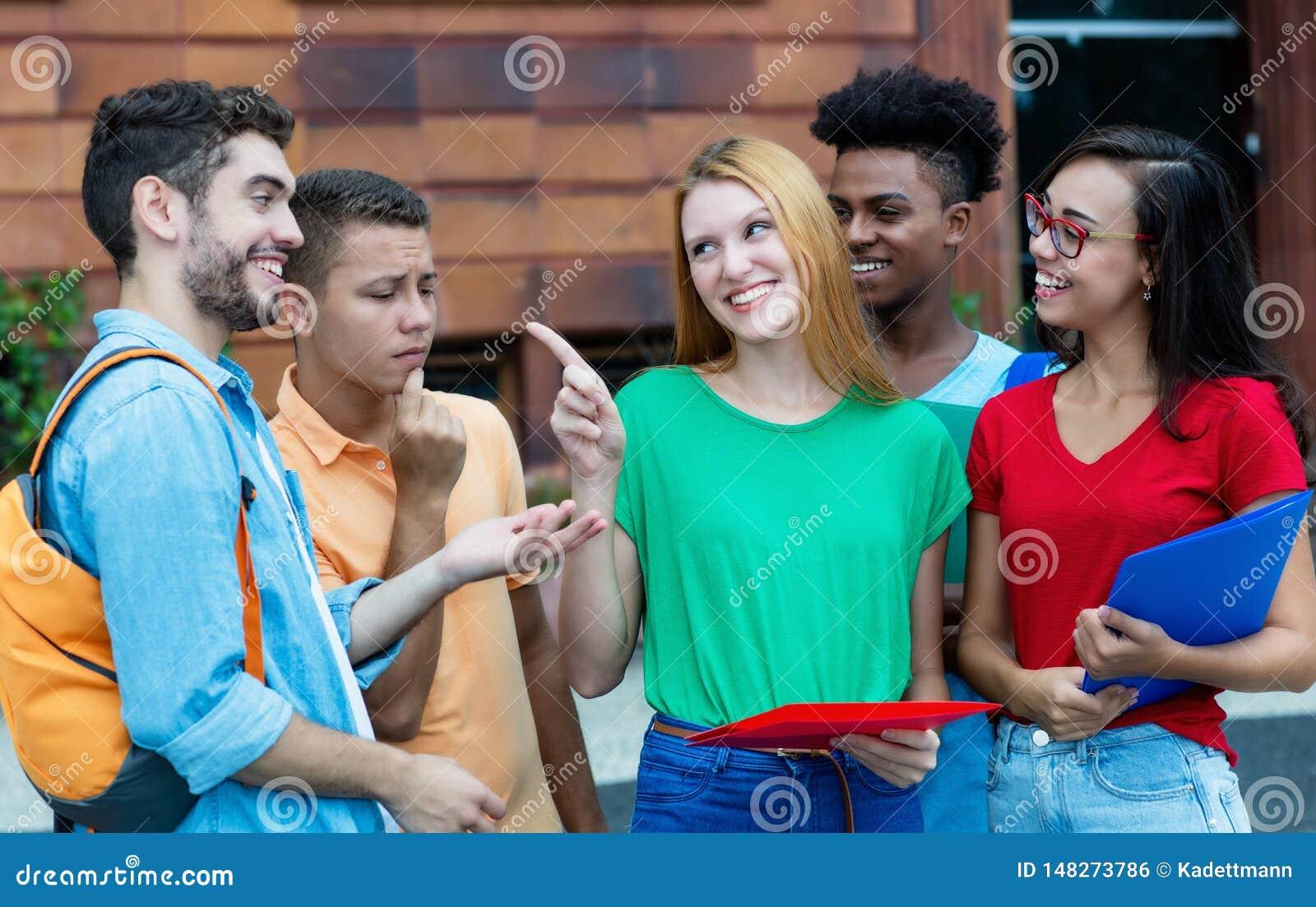 Grupp av caucasian och latin- och afrikansk amerikanstudenter som talar om läxa