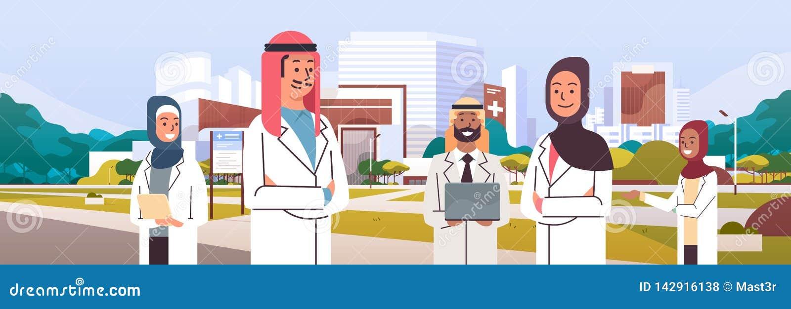 Grupp av det arabiska doktorslaget i likformign som tillsammans framme står av sjukhuset som bygger yttersida för medicinsk klini