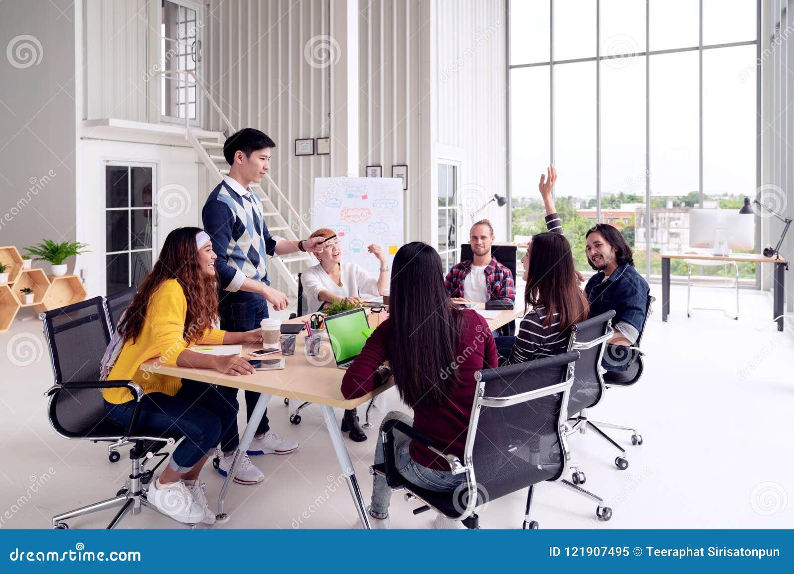 Grupp av det blandras- unga idérika laget som talar, skrattar och idékläckning i möte på det moderna kontorsbegreppet kvinnligt a