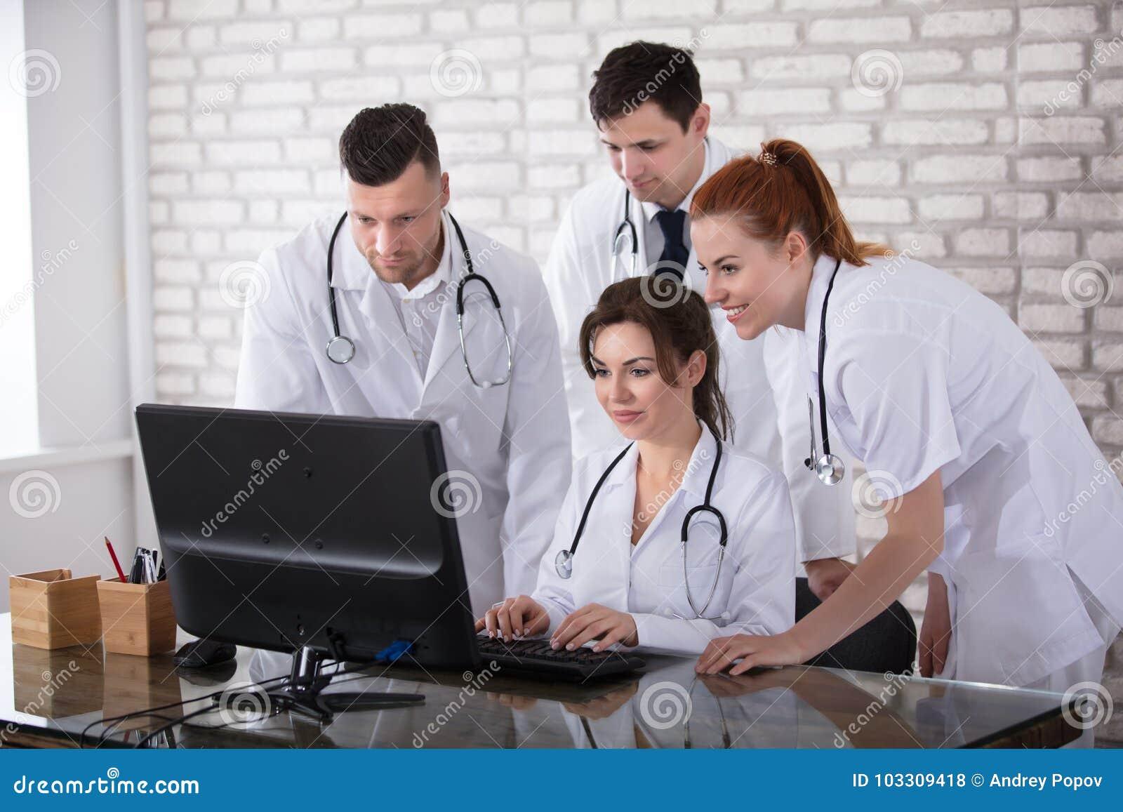 Grupp av doktorer som ser datoren
