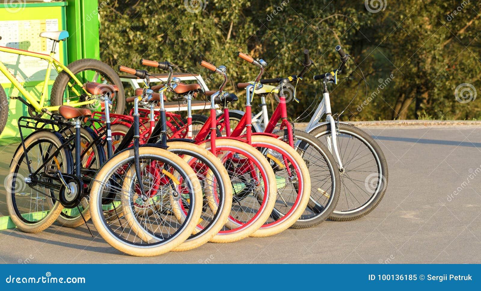 Grupp av färgrika cyklar som tillsammans parkeras i en parkeringsplatscloseup