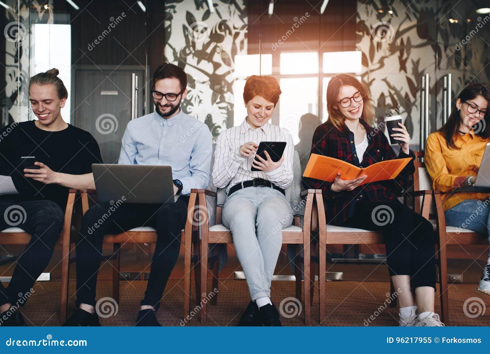 Grupp av fem moderna studenter som arbetar i ett vindrum Idérik t
