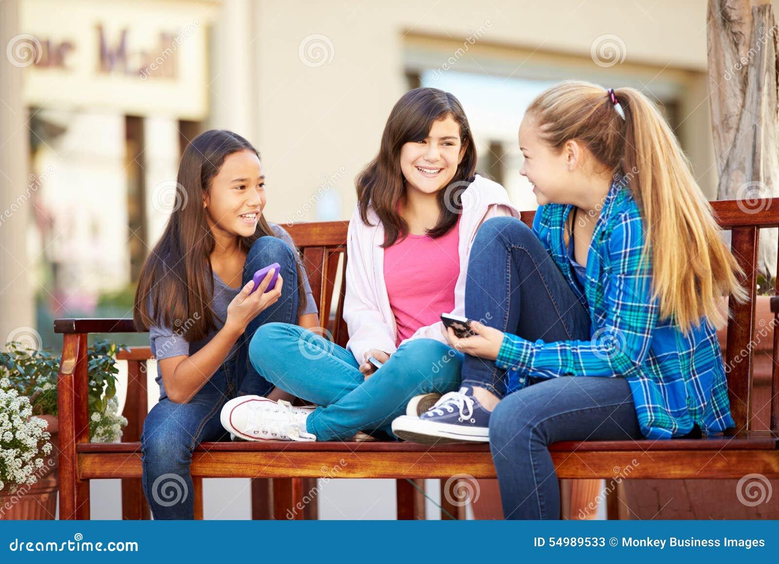 Grupp av flickor som sitter i galleria genom att använda mobiltelefoner