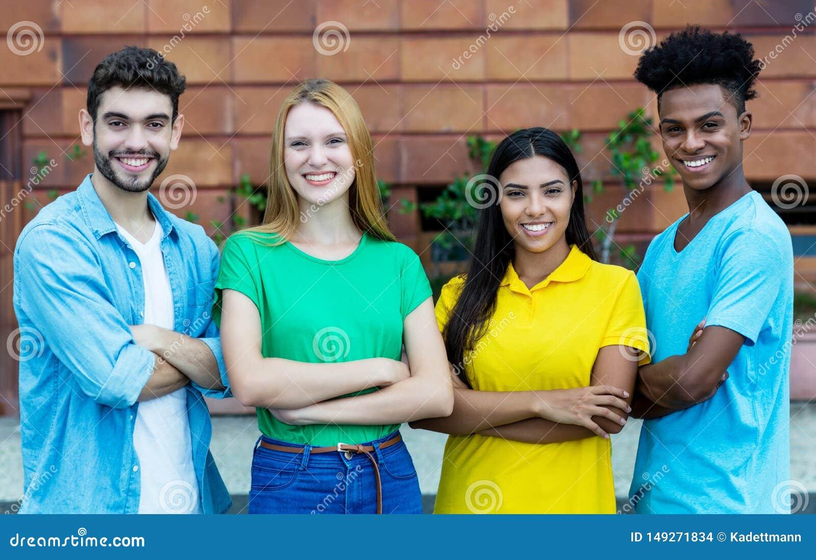 Grupp av fyra afrikansk amerikan och latin och caucasian unga vuxna m?nniskor