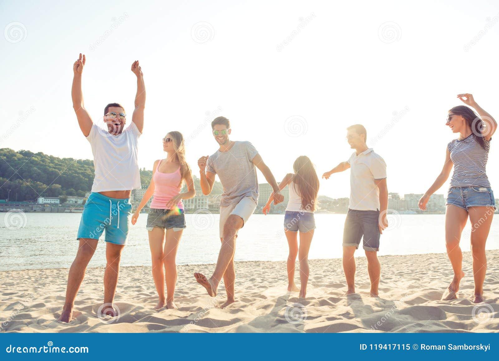 Grupp av gladlynt folk som har partiet och att dansa för strand