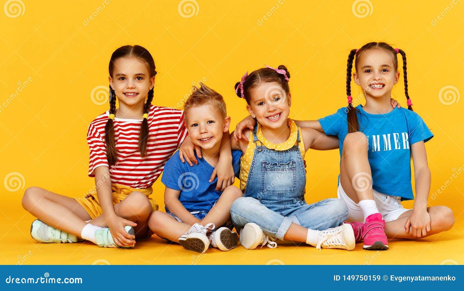 Grupp av gladlynta lyckliga barn p? kul?r gul bakgrund