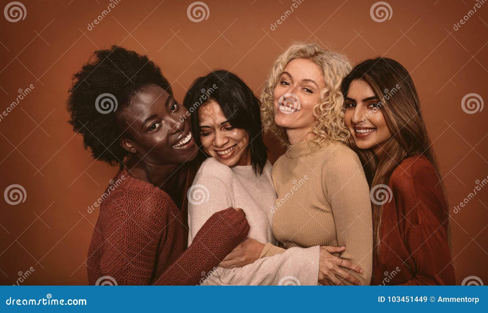 Grupp av gladlynta unga kvinnor som tillsammans står
