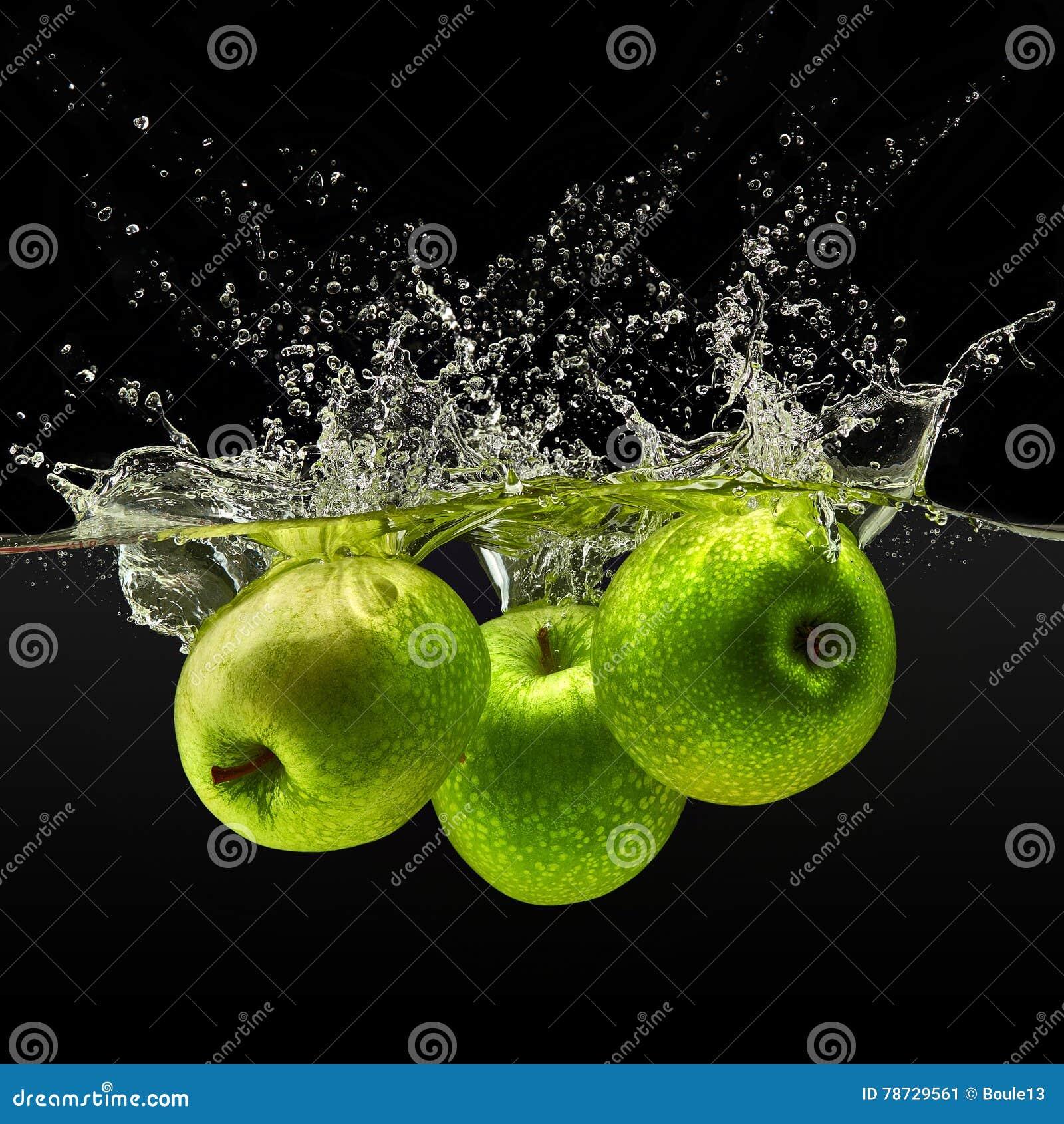 Grupp av gröna äpplen som faller i vatten på svart