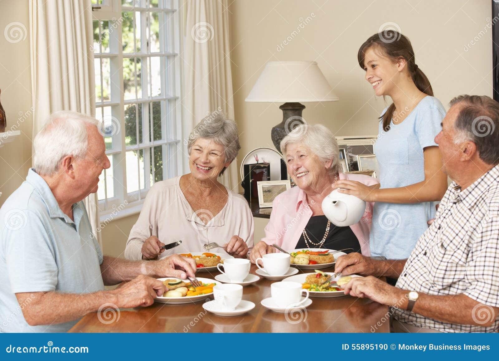 Grupp av höga par som tillsammans tycker om mål i omsorghem med den tonårs- hjälpredan
