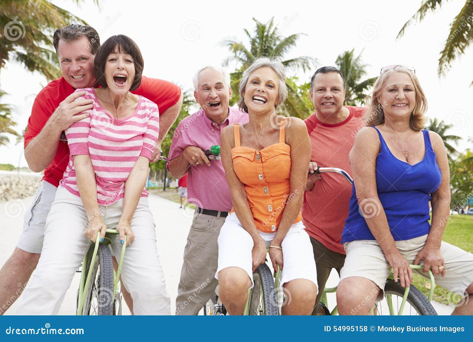 Grupp av höga vänner som har gyckel på cykelritt