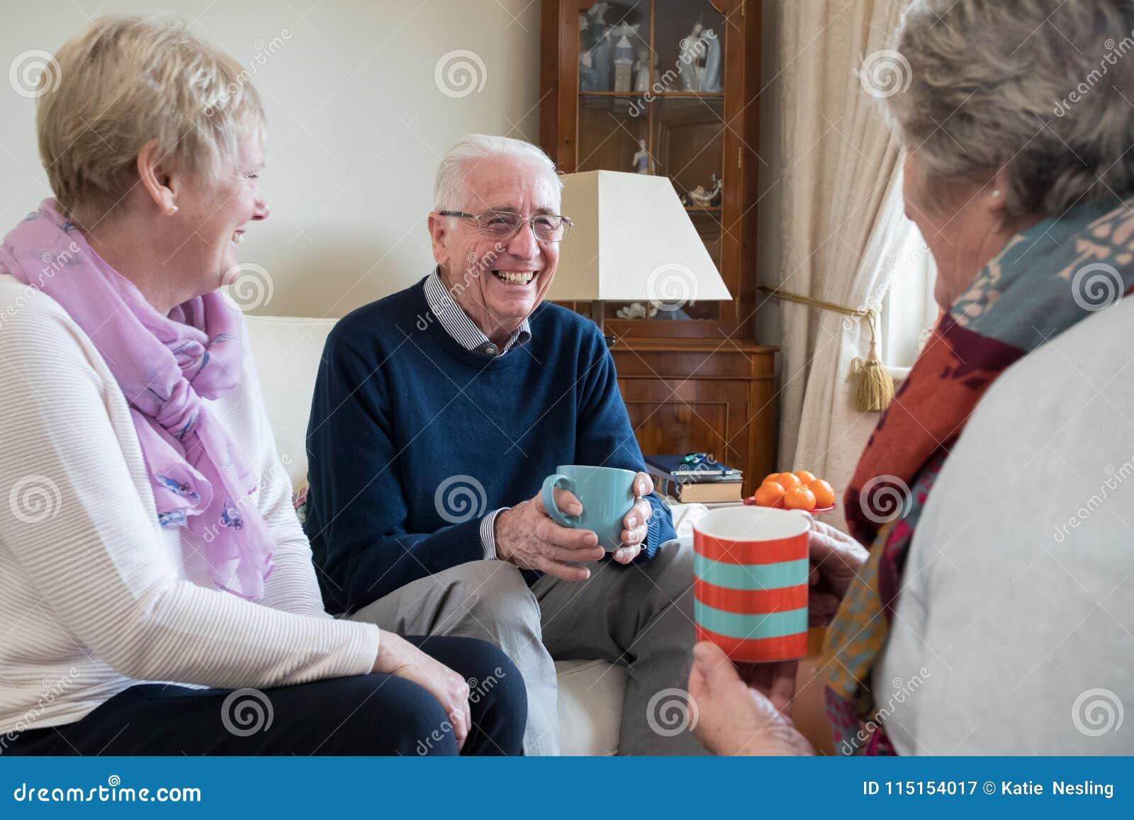 Grupp av höga vänner som hemma möter för kaffe