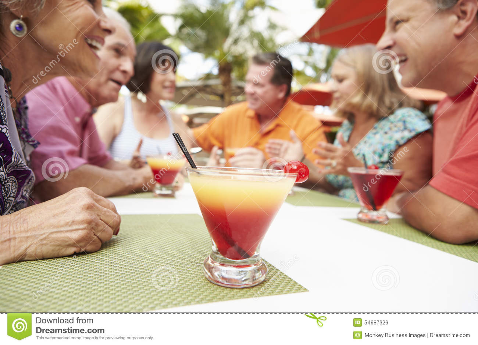 Grupp av höga vänner som tillsammans tycker om coctailar i stång