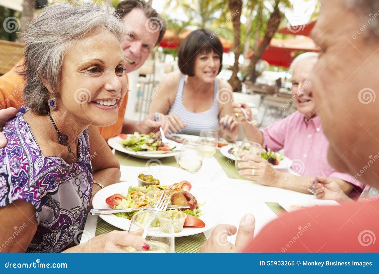 Grupp av höga vänner som tycker om mål i utomhus- restaurang