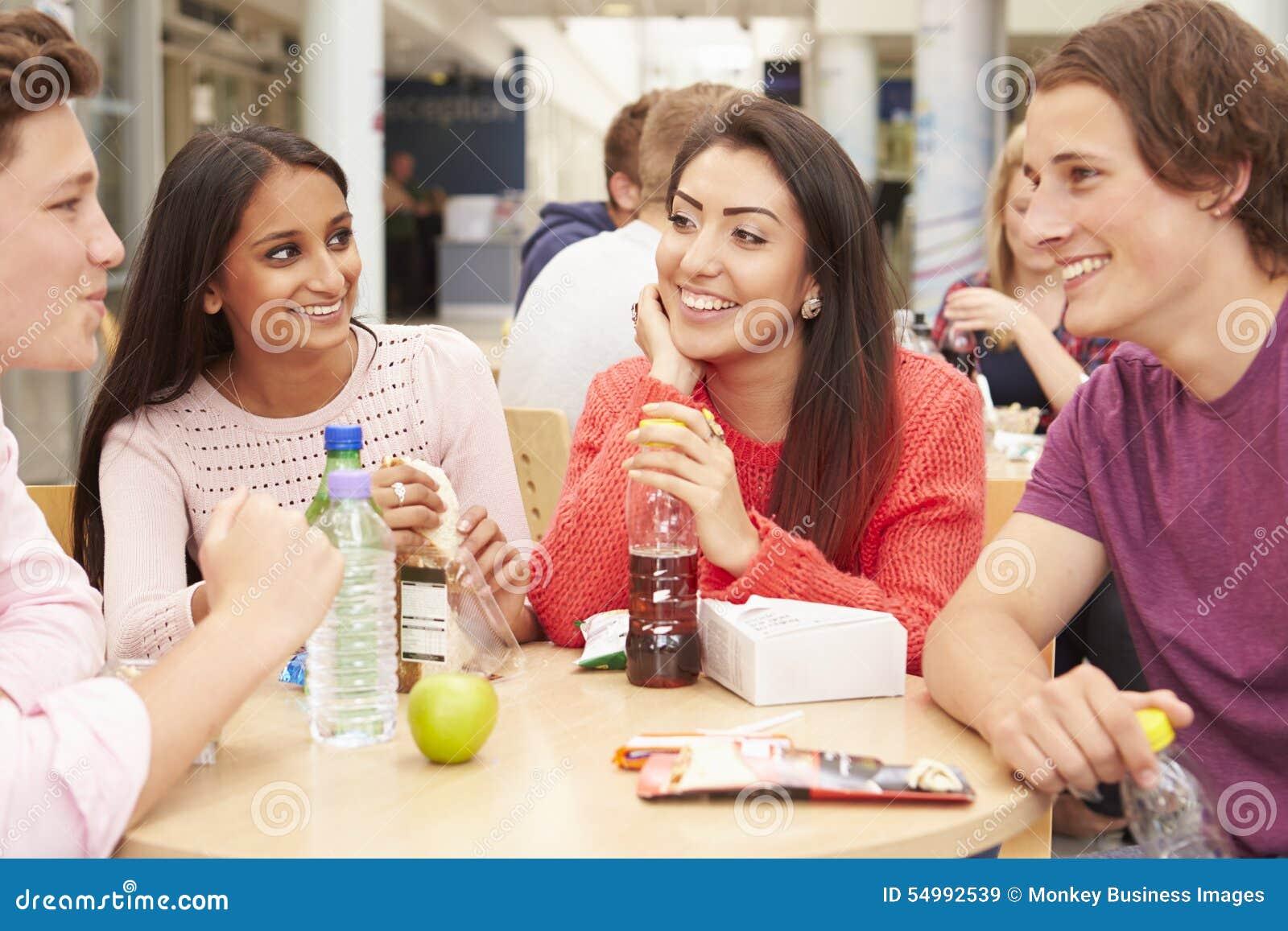 Grupp av högskolestudenter som tillsammans äter lunch