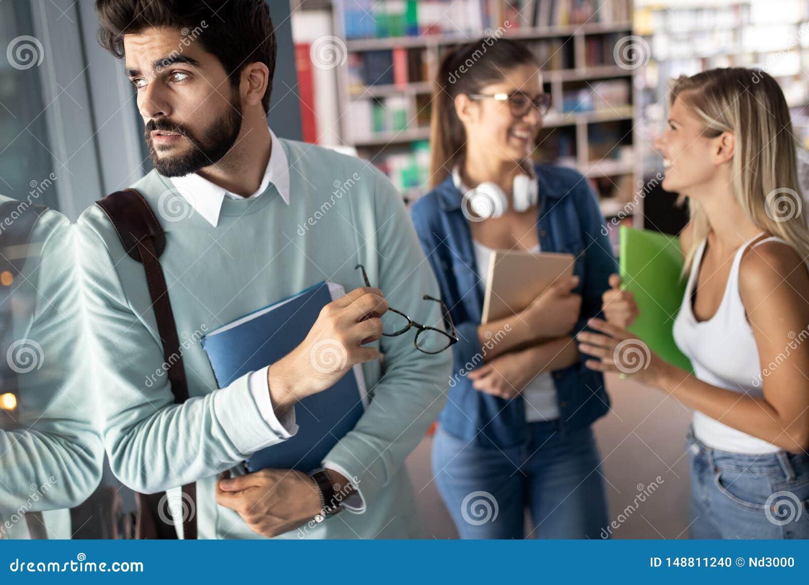 Grupp av högskolestudenter som tillsammans studerar och läser books isolerad white f?r begrepp utbildning