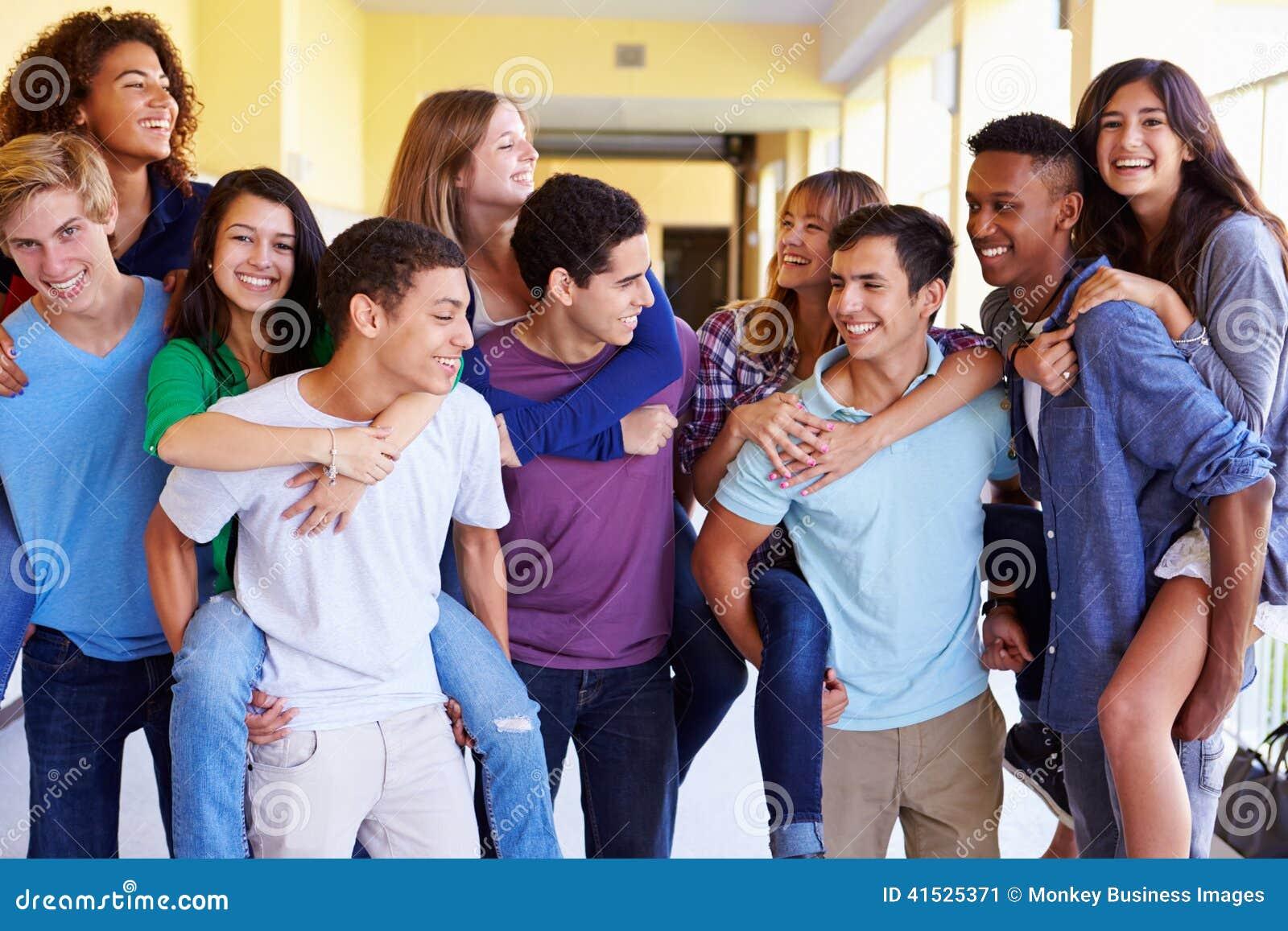 Grupp av högstadiumstudenter som ger ridturer på axlarna i korridor