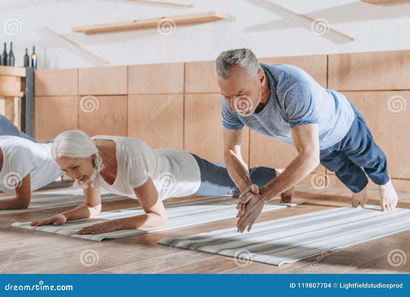 Grupp av högt folk som gör plankan på yogamats