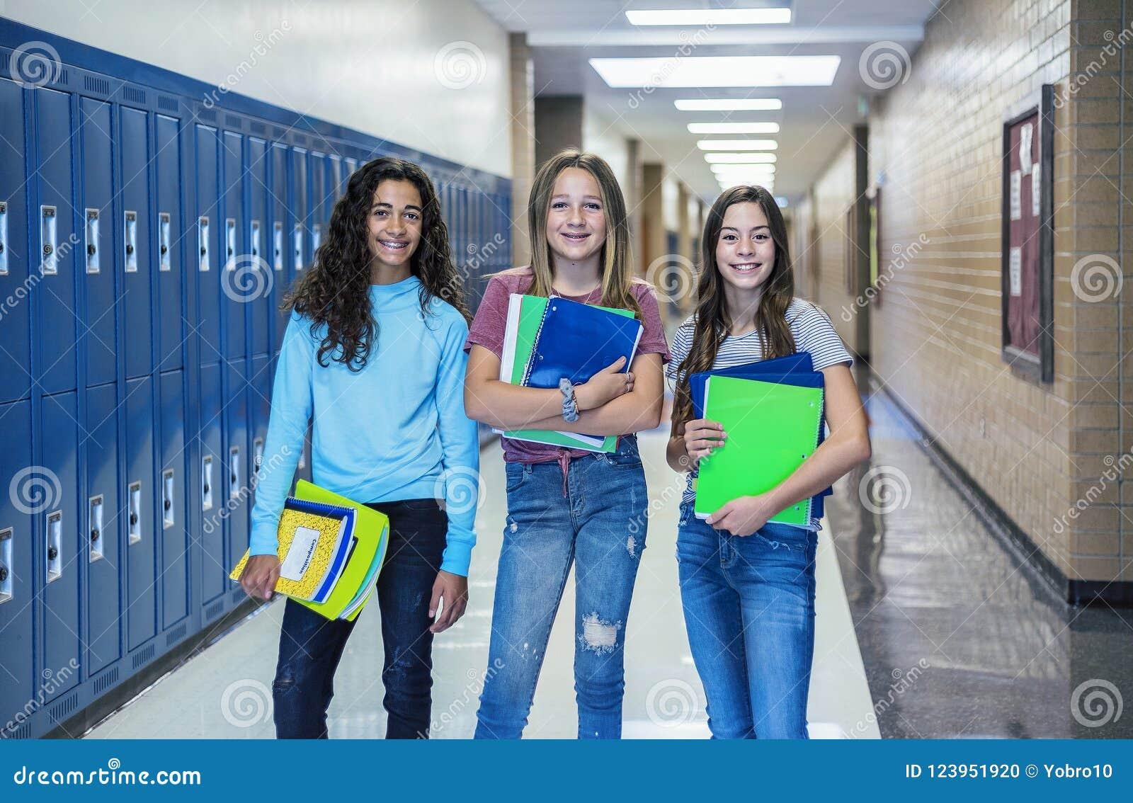 Grupp av Junior High skolastudenter som tillsammans står i ett skolahall