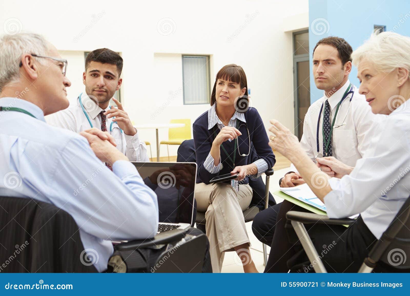 Grupp av konsulenter som sitter på tabellen i sjukhusmöte