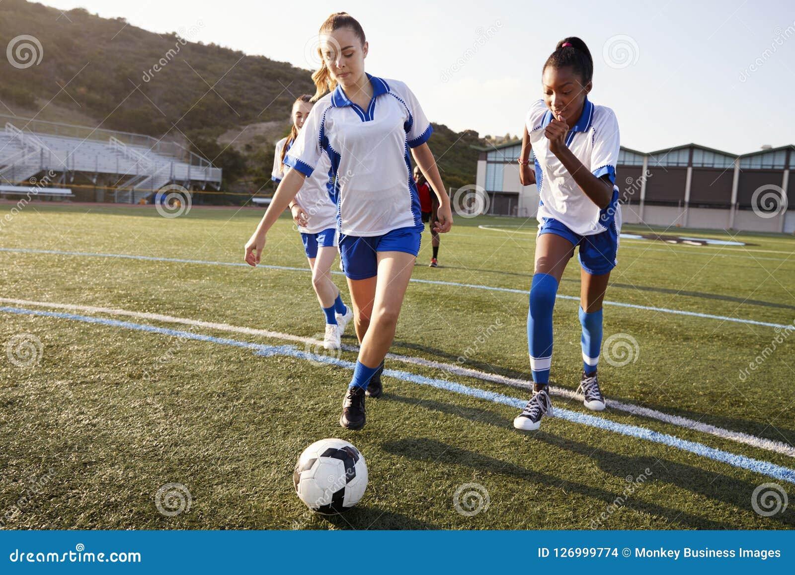 Grupp av kvinnliga högstadiumstudenter som spelar i fotbolllag