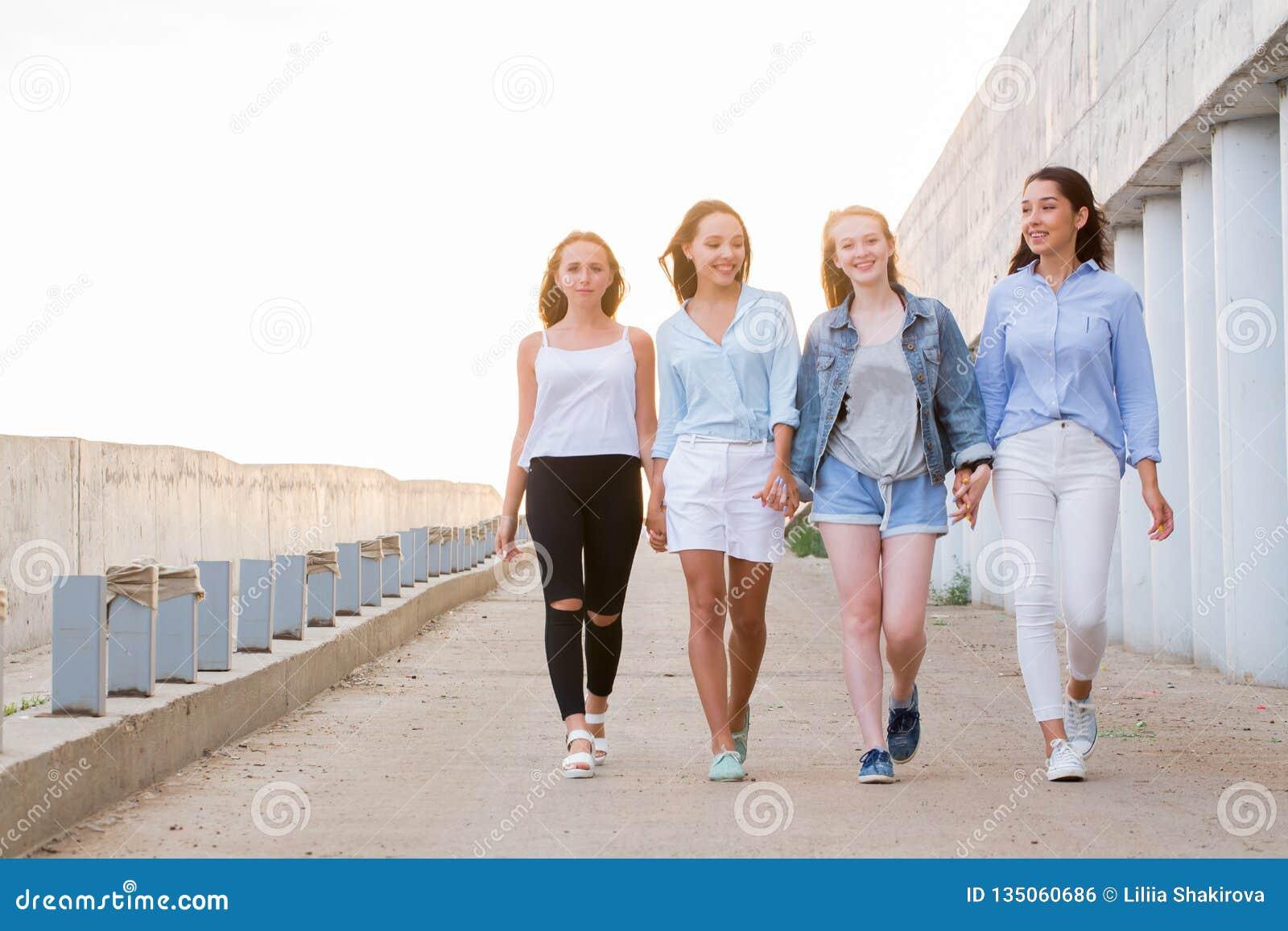 Grupp av kvinnligt gå för vänner som är utomhus- och att tala och att ha gyckel och leende togethernes kamratskap, livsstilbegrep