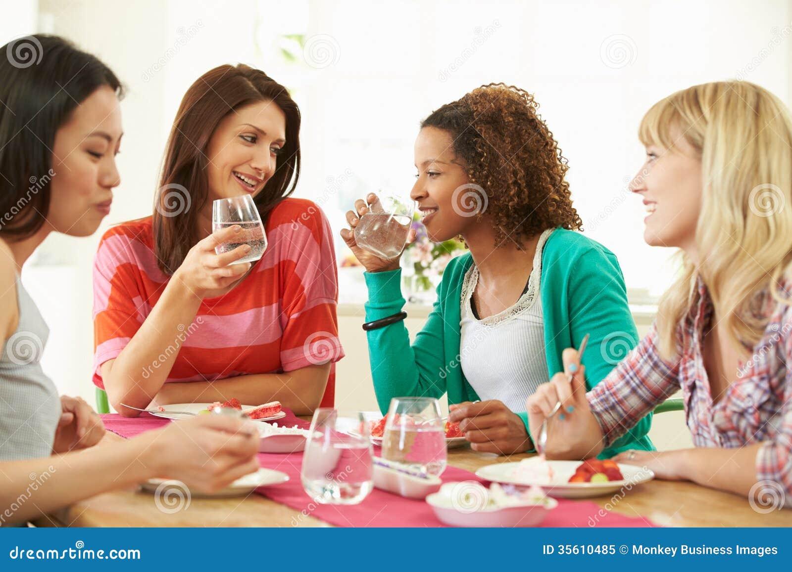 Grupp av kvinnor som sitter runt om tabellen som äter efterrätten