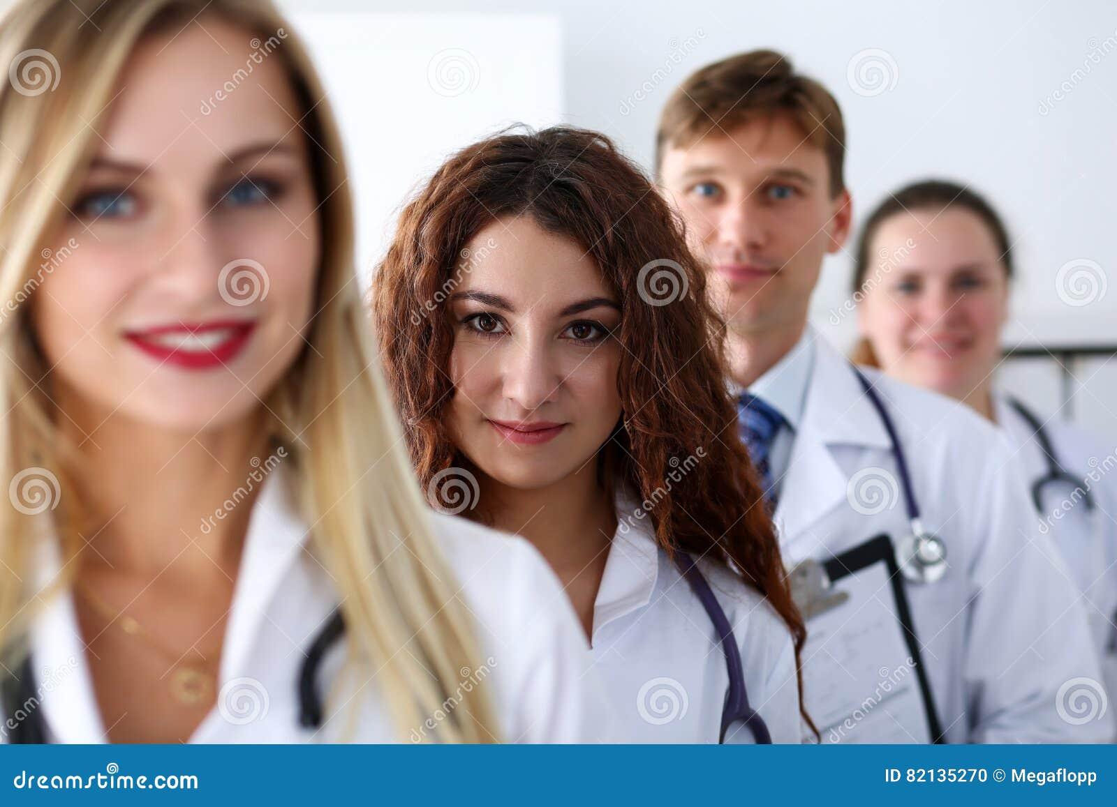 Grupp av läkare som poserar proudly i rad och in camera ser smil