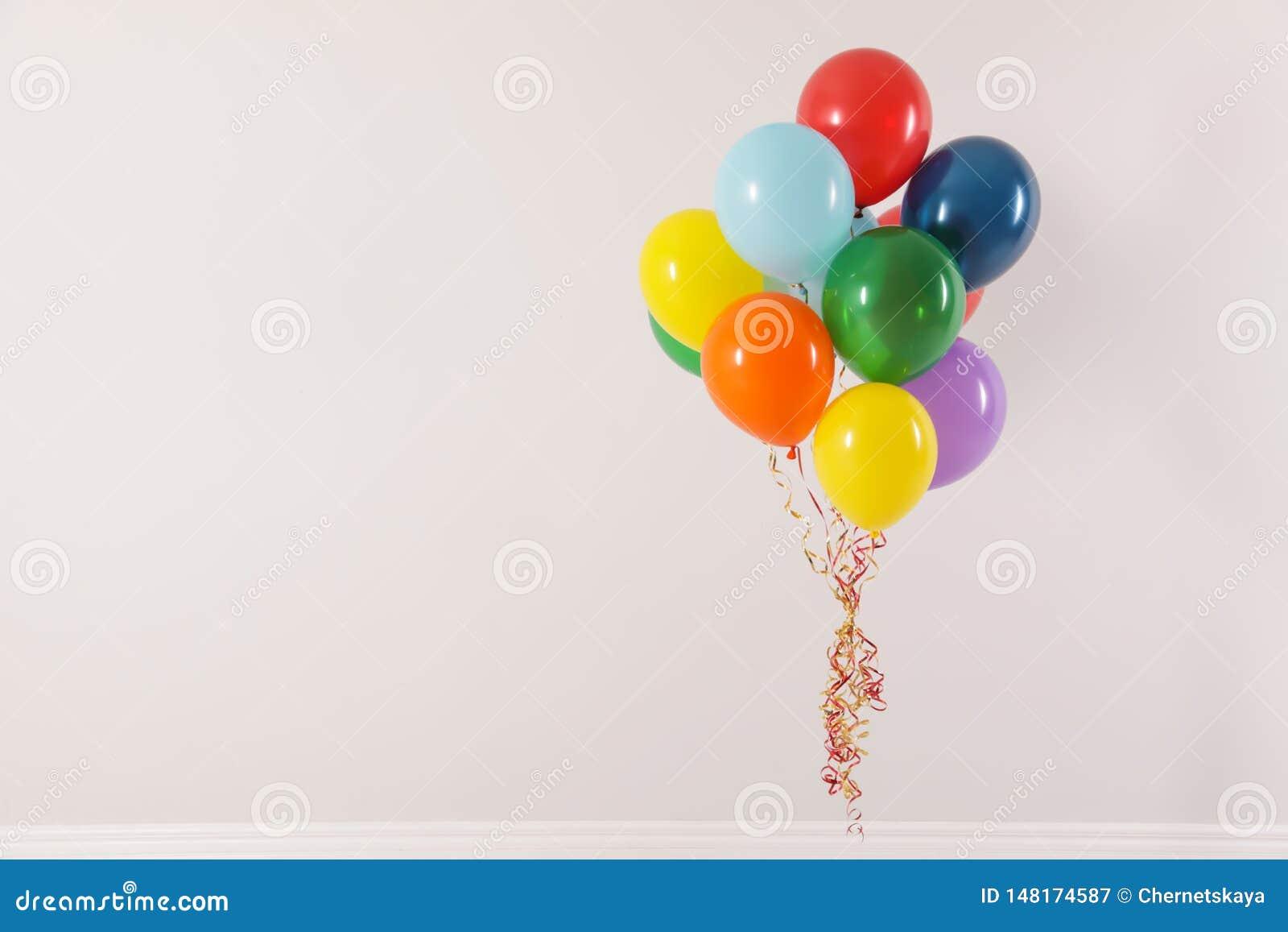 Grupp av ljusa ballonger p? ljus bakgrund Ber?mtid