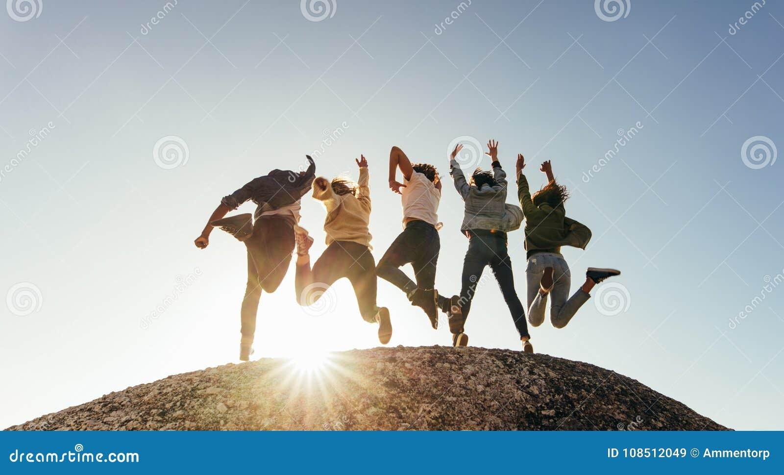 Grupp av lyckliga vänner som har gyckel på bergöverkant