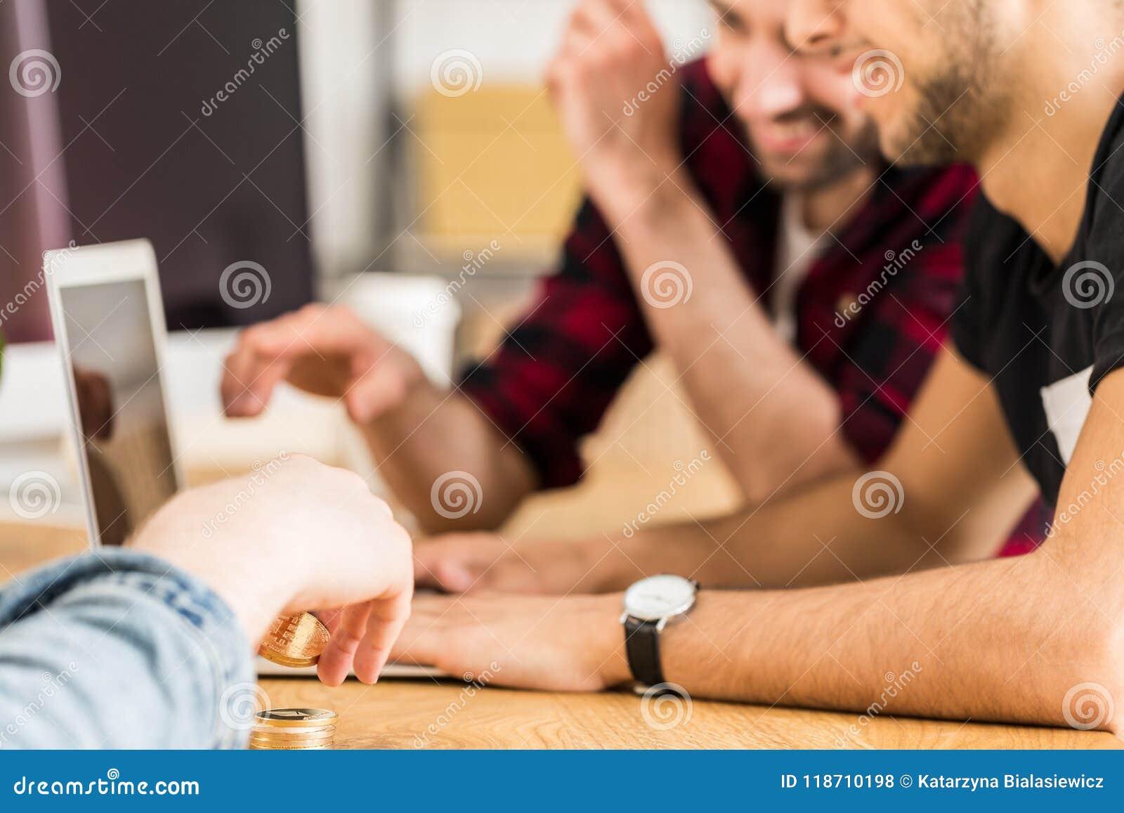 Grupp av lyckliga vänner som tillsammans framme sitter av en bärbar dator E