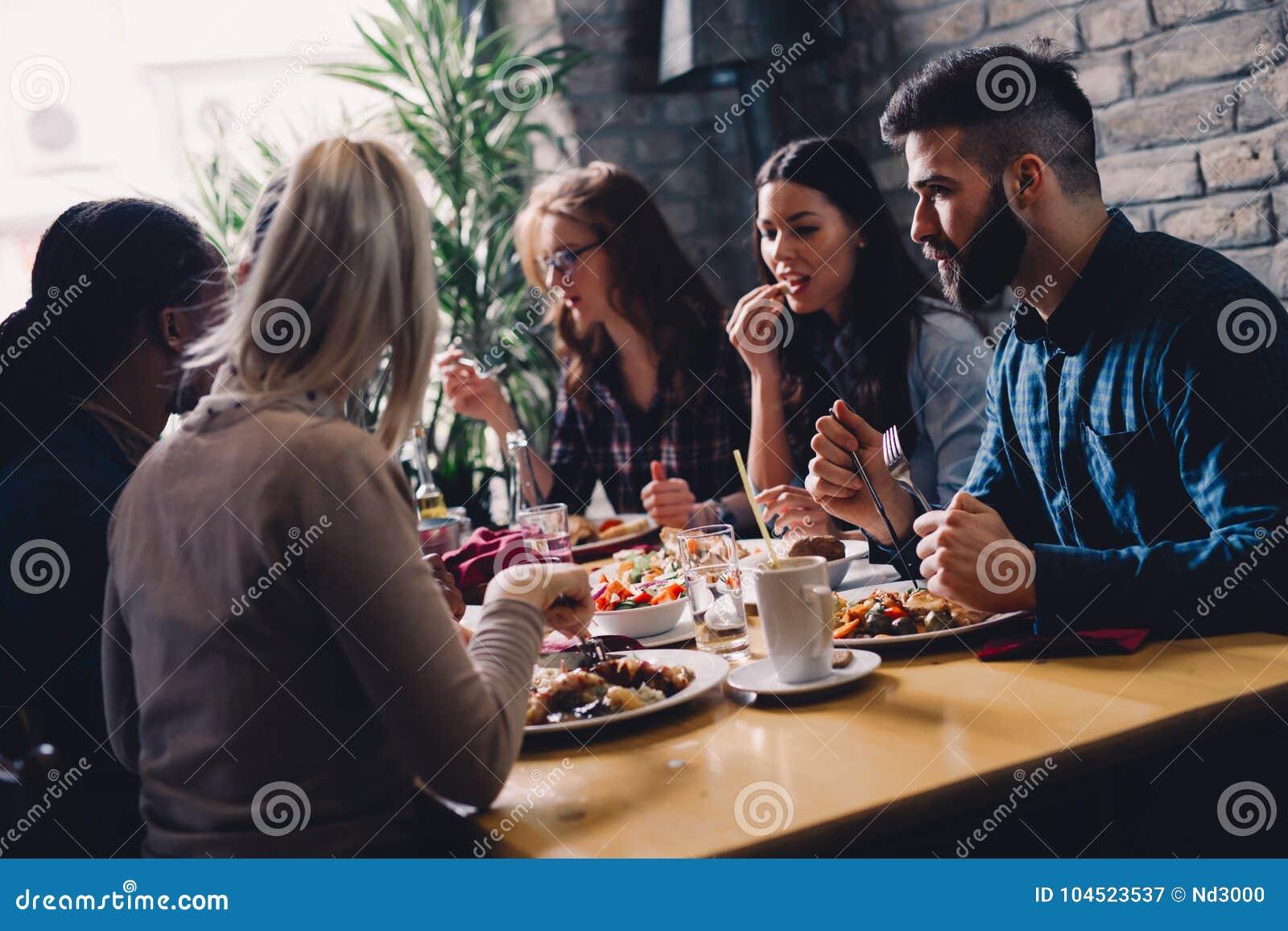 Grupp av lyckligt affärsfolk som äter i restaurang
