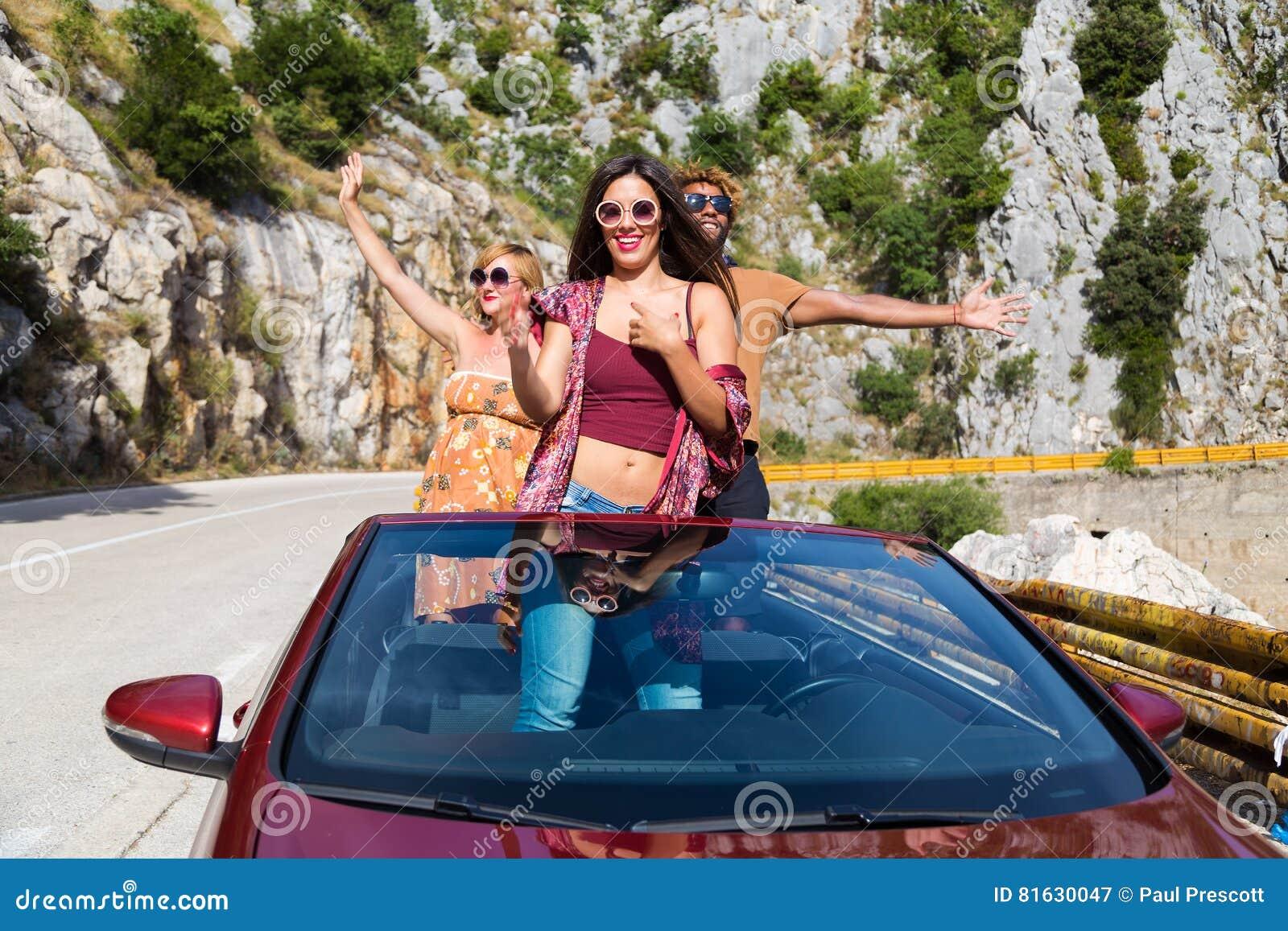 Grupp av lyckligt folk i röd konvertibel bil