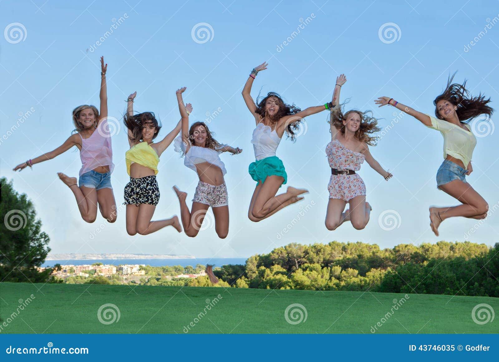 Grupp av lyckligt hoppa för tonår,