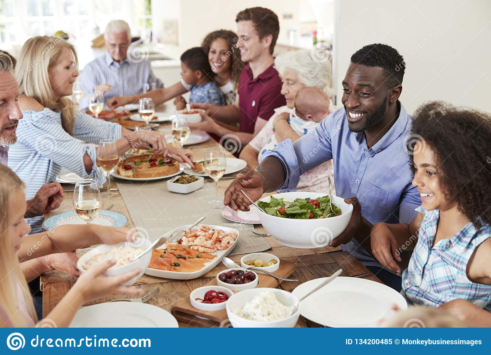 Grupp av Mång--utveckling familj och vänner som sitter runt om tabellen och tycker om mål